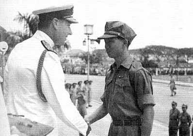Un giovane Chin Peng è accolto da un ufficiale britannico al termine della guerra